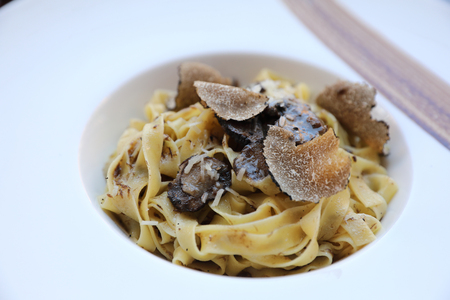 pasta with black truffles on wood background , Italian food