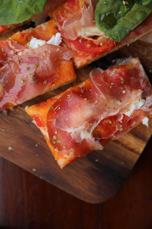 Pizza with parma ham salad rocket and parmesan on dark wooden background close up. Italian food