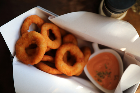 Onion rings with sauce on wooden table