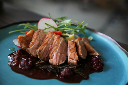 Duck confit with salad , baked apple and raspberry sauce served on wooden table