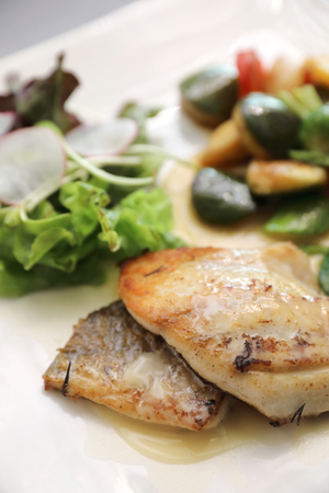 Sea bass fillet with grilled vegetables and salad on wooden table Stock Photo