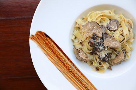 pasta with black truffles on wood background , Italian food