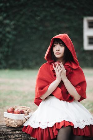 Ritratto di giovane donna con costume da Cappuccio Rosso nel parco di alberi verdi green Archivio Fotografico