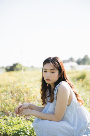 Portrait of Young Asian woman girl sitting and smile in flower garden Stock Photo