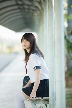 Portrait of asian japanese school girl costume sitting and looking at park outdoor 版權商用圖片