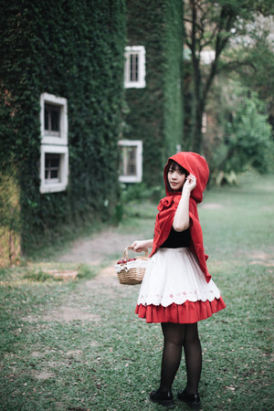 Portrait young woman with  Red  Hood costume in green tree park Stok Fotoğraf