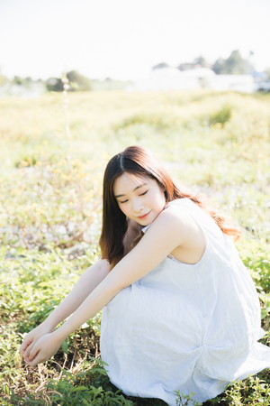 Portrait of Young Asian woman girl sitting and smile in flower garden Stock Photo - 124616331