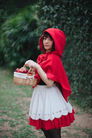 Retrato de mujer joven con traje de Caperucita Roja en Green Tree Park