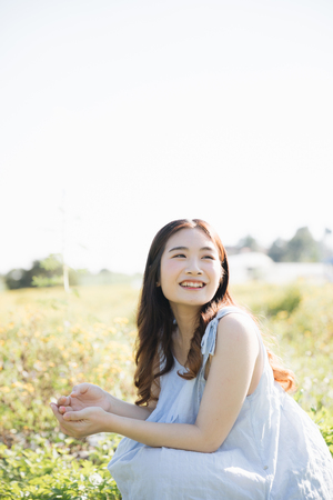 Portrait of Young Asian woman girl smile in flower garden Stock Photo - 124619253