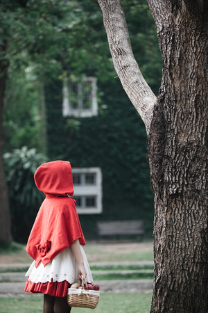 Portrait young woman with  Red  Hood costume in green tree park Stock Photo