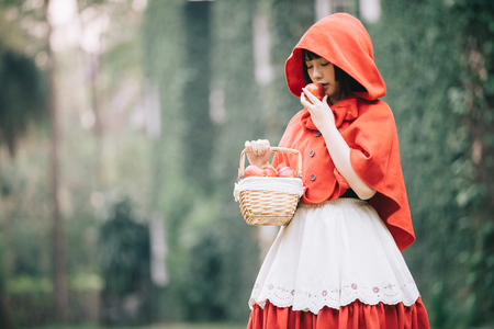 Ritratto di giovane donna con costume da Cappuccio Rosso nel parco di alberi verdi green