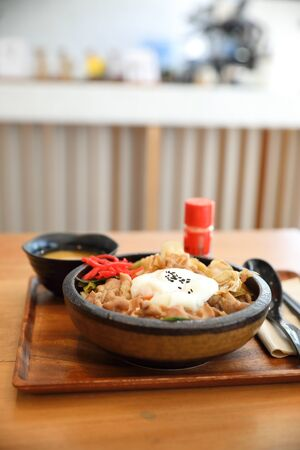 Japanese food Gyudon Japanese beef on rice bowl topped with egg on wooden table