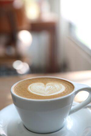 Cappuccino oder Latte Art Kaffee aus Milch auf dem Holztisch im Café Standard-Bild