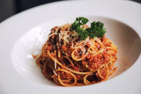 spaghetti Bolognese with minced beef and tomato sauce garnished with parmesan cheese and basil, Italian food