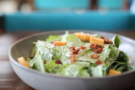 Caesar salad with crispy bread and bacon close up on wood background