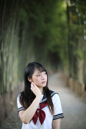 Portrait of beautiful Asian japanese high school girl uniform looking with bamboo forest background Stock fotó - 150634629