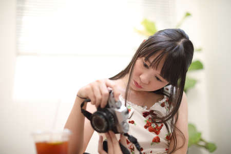 Portrait of Asian young woman with camera in coffee shop