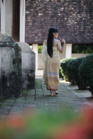 Portrait of Thai female with traditional Thai dress walking with temple background Stock fotó