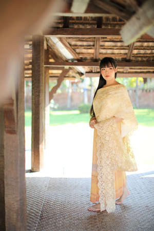 Portrait of Thai female with traditional Thai dress with temple background Stock fotó