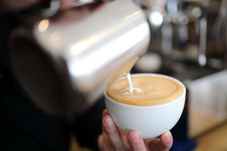 Male hands pouring milk and preparing to making cappuccino coffee