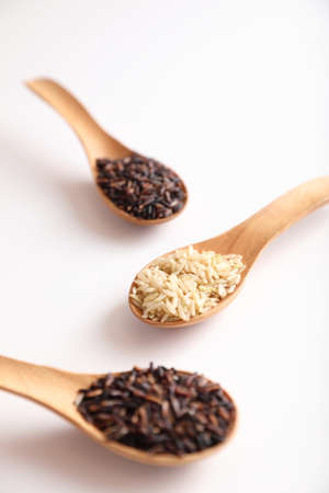 Organic raw brown rice and riceberry rice on spoon in close up