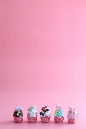 Colorful cupcakes isolated in pink background