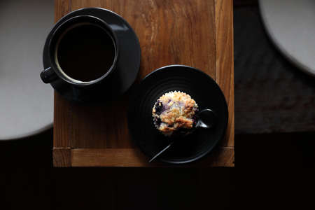 Coffee cup with muffin on wood table in local coffee shop