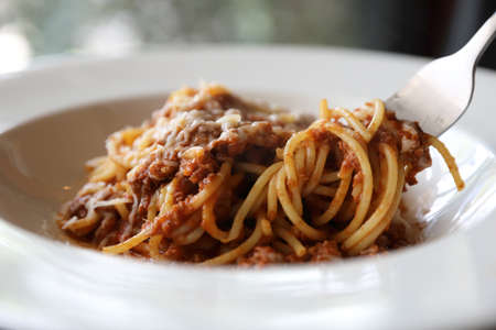 spaghetti Bolognese with minced beef and tomato sauce garnished with parmesan cheese and basil Stockfoto