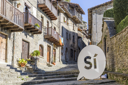 RUPIT, SPAIN - OCTOBER 29, 2017: The Catalan National Assemblys pro-independence Si logo on the streets of the medieval Rupit village