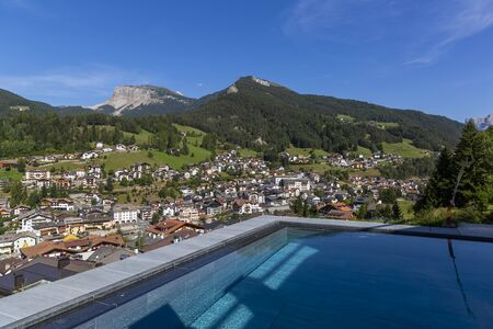 Swimming pool in the Dolomites with a view of Ortisei, South Tyrol, Italy