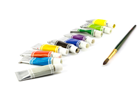Tubes of  colored paint and brush on white background photo