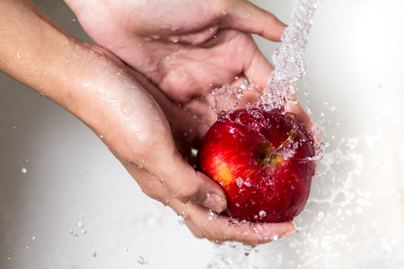 fruit water: Female hands washing apple
