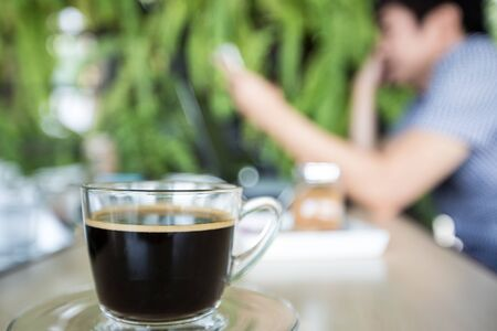 bussiness man: cup of coffee with man use cell phone background