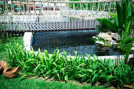 bridge in nature: Beautiful classical design garden fish pond in a gardening background and hanging wooden bridge