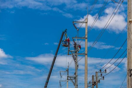 stays: Electrician stays on the tower pole and repairs a wire of the power line
