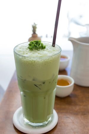 matcha: Green tea smoothie on a wooden table