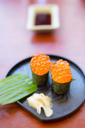 Sushi with caviar on a black plate with ginger