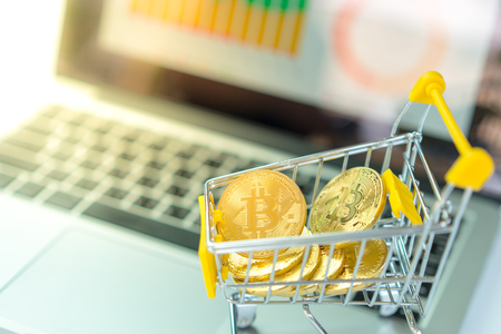 bitcoin in the shopping cart computer background with golden light Stock Photo
