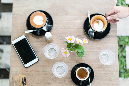 hot coffee in black mug and smart phone on wooden table Stock Photo - 97914383