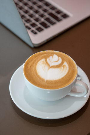 Hot art latte coffee cup on wooden table