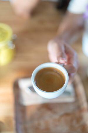 Hot espresso coffee on women hand holder