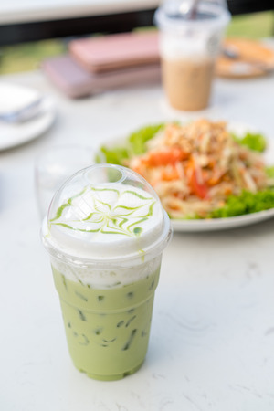 Iced green tea and food on table