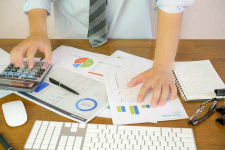 Businessman hand working with finances about cost and calculator budget