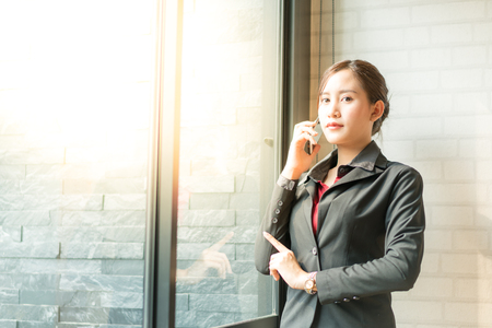 Business woman holding cell phone to call with customer in working time Фото со стока