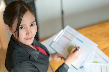Business woman holding a pencil is working with business chart graph checking infomation inside is working with business chart graph checking infomation inside Фото со стока