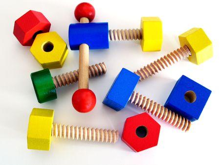 juguetes de madera: Tornillos de madera coloreados de los juguetes - amarillos, rojos, azules y verdes Foto de archivo