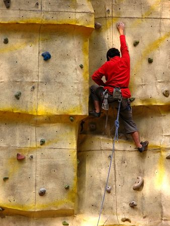 Boys with a red sweat climbing an artificial rock wall  photo
