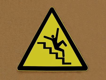 descend: Yellow and black caution sign isolated on a brown wall