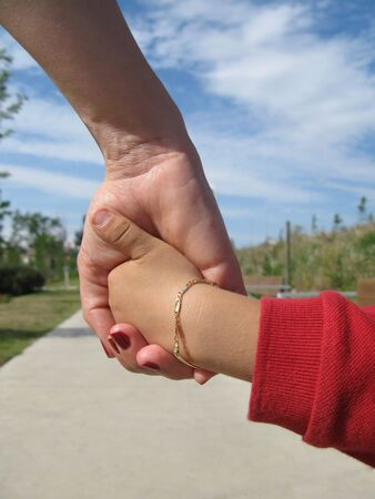 child care: Mom and his young son holding hands
