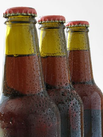 Three bottles of fresh beer with caps - focus on the second bottle photo